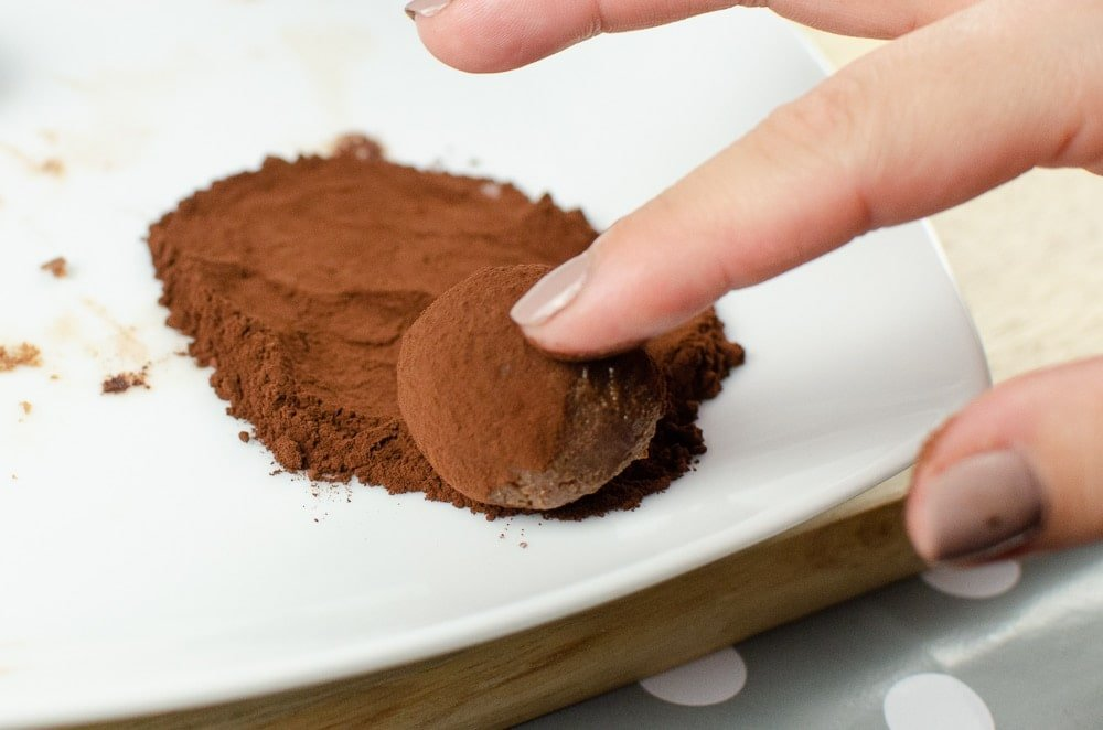 Dusting our milk chocolate truffles with coco powder  on a white plate