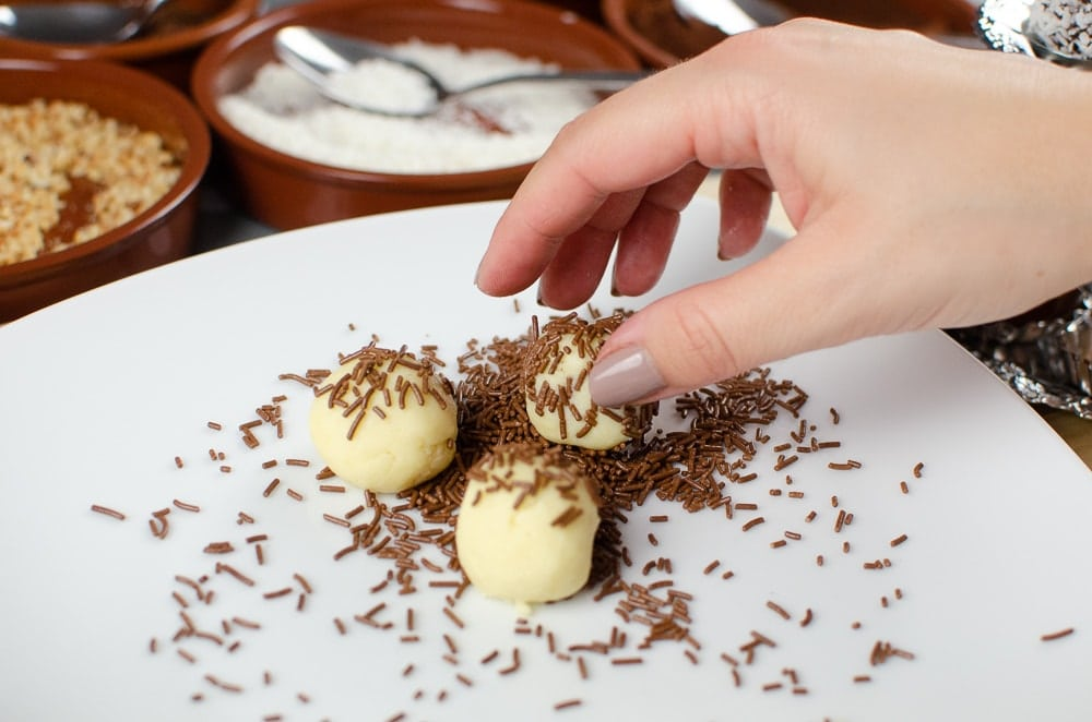 Rolling the white chocolate truffles in chocolate sprinkles on a white plate