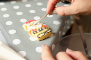 Decorating Joie christmas santa biscuit with royal icing. Xmas Cookie