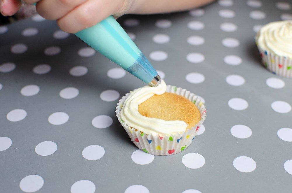 piping the buttercream topping on the children in need cupcakes