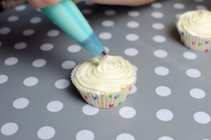 piping the buttercream topping on the cupcakes