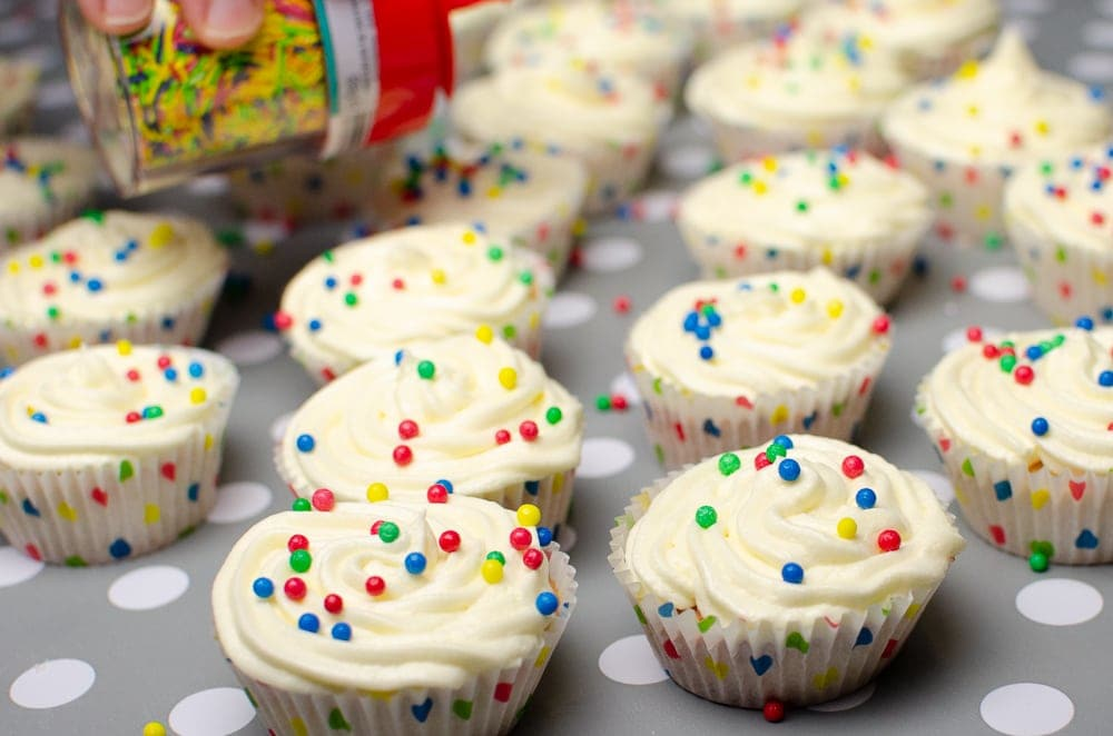 sprinkles being poured over the cupcakes