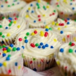 Cupcakes with white frosting with multi colour balls on top