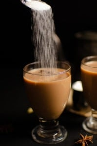 Sugar being poured into the masala tea in a glass