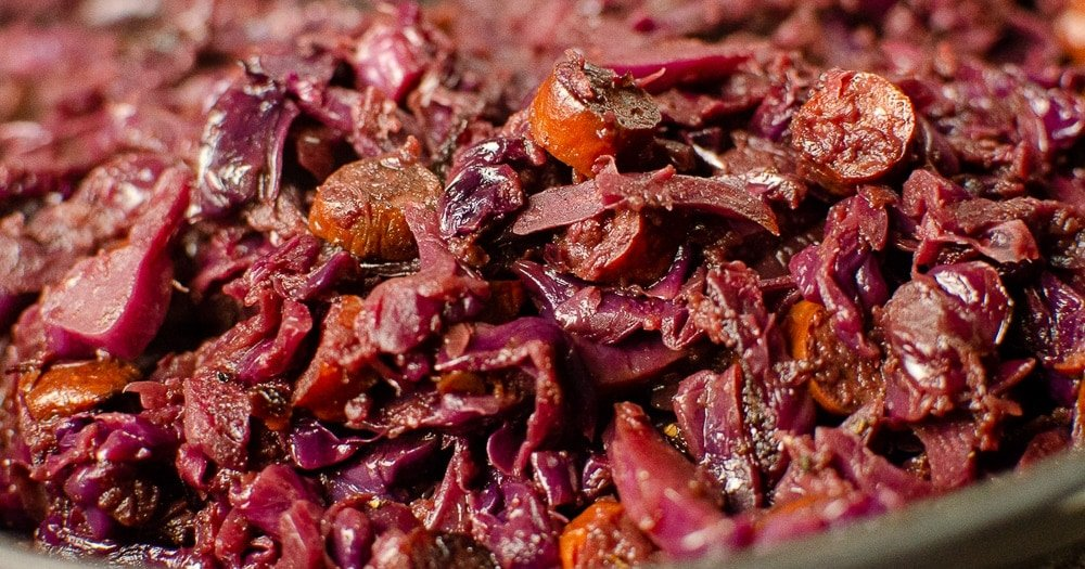 Red Cabbage with Apple and Kabonas cooking in a cast iron pan