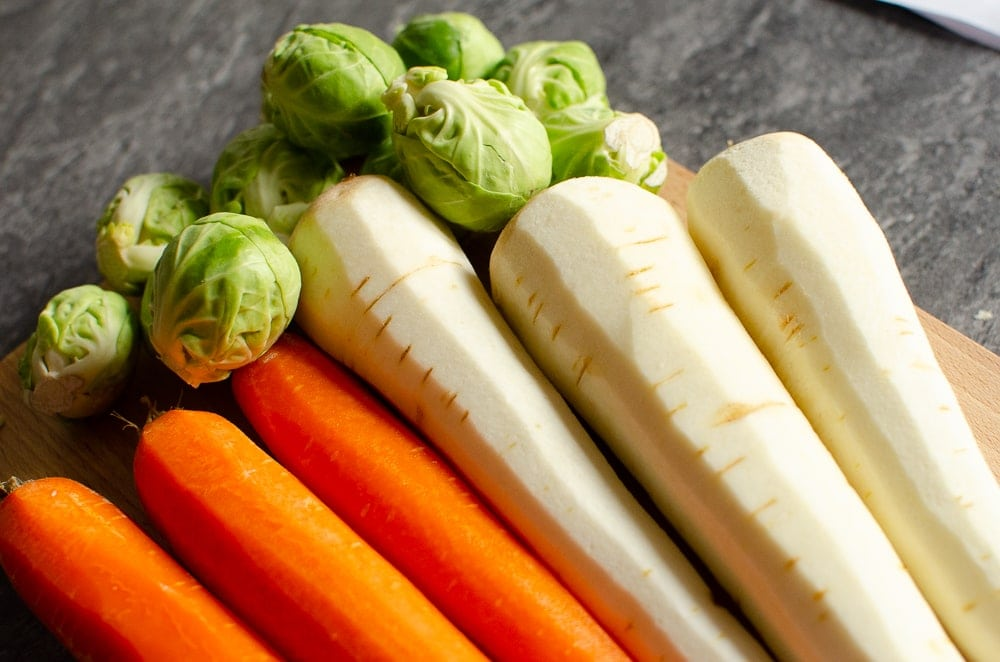 Brussel Sprouts, Peeled Carrots and Parsnips on a wooden chopping board