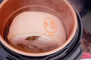 Gammon joint in a pressure cooker pot with a bay leaf on top