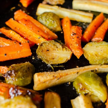 roasted carrots,parsnips and brussel sprouts with maple and rosemary glaze on a black baking tray