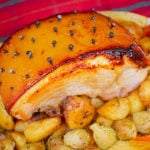 Glazed gammon joint recipe with roast potatoes and vegetables on a tartan table cloth