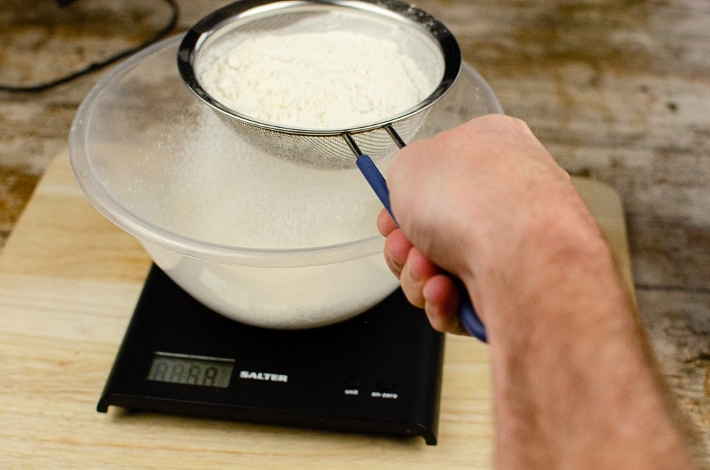 Plain flour being sieved into a plastic mixing bowl on black scales on a wooden chopping board