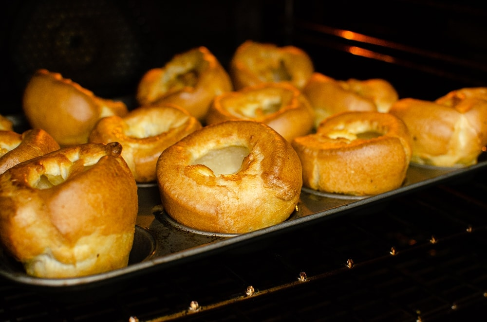 Flawless Yorkshire puddings cooking in the oven on a silver tray