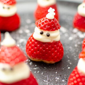 Strawberries with cream in the middle made into little santas with chocolate eyes