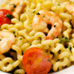 Pesto King Prawn Pasta served in a white bowl, with tomatoes