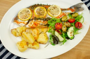 sea bream cooked with chilli and garlic with lemon on top. Served with roast potatoes and salad