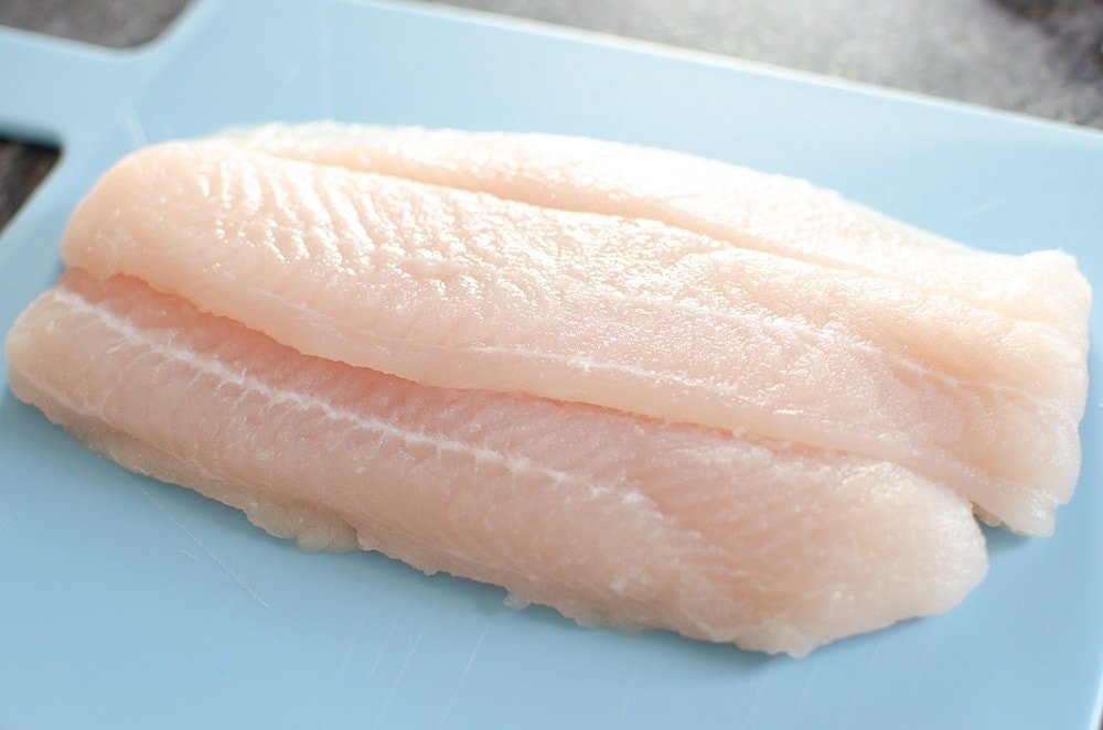 Basa Fish on a blue chopping board to be cut