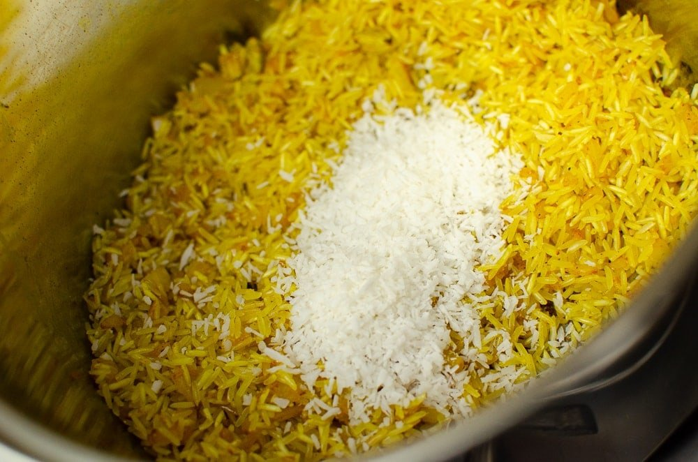 Coconut Pilau Rice with coconut on top cooking in a silver pot