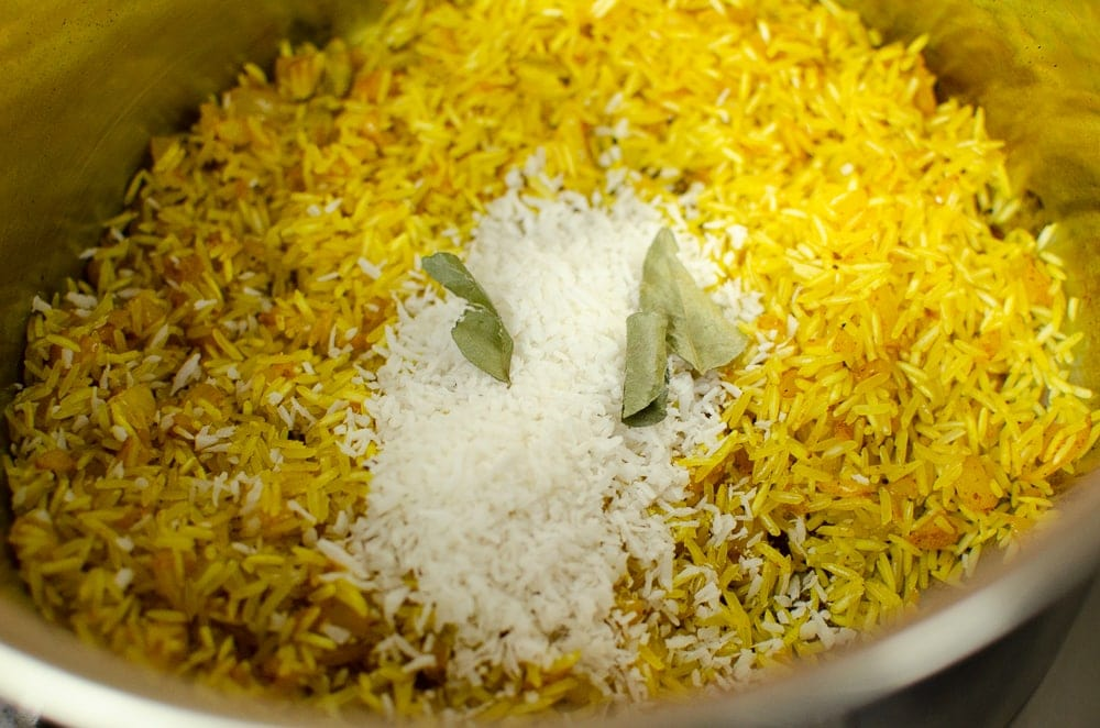 Coconut Pilau Rice with coconut and curry leaves on top cooking in a silver pot