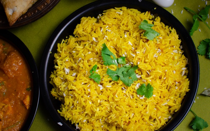 Coconut Pilau Rice with chopped coriander and coconut sprinkled ontop in a black serving dish