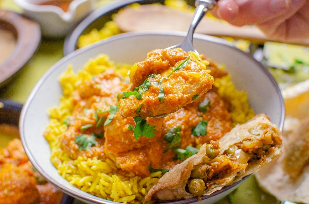 Basa Fish Curry in a bowl with rice and samosa being served with a silver spoon