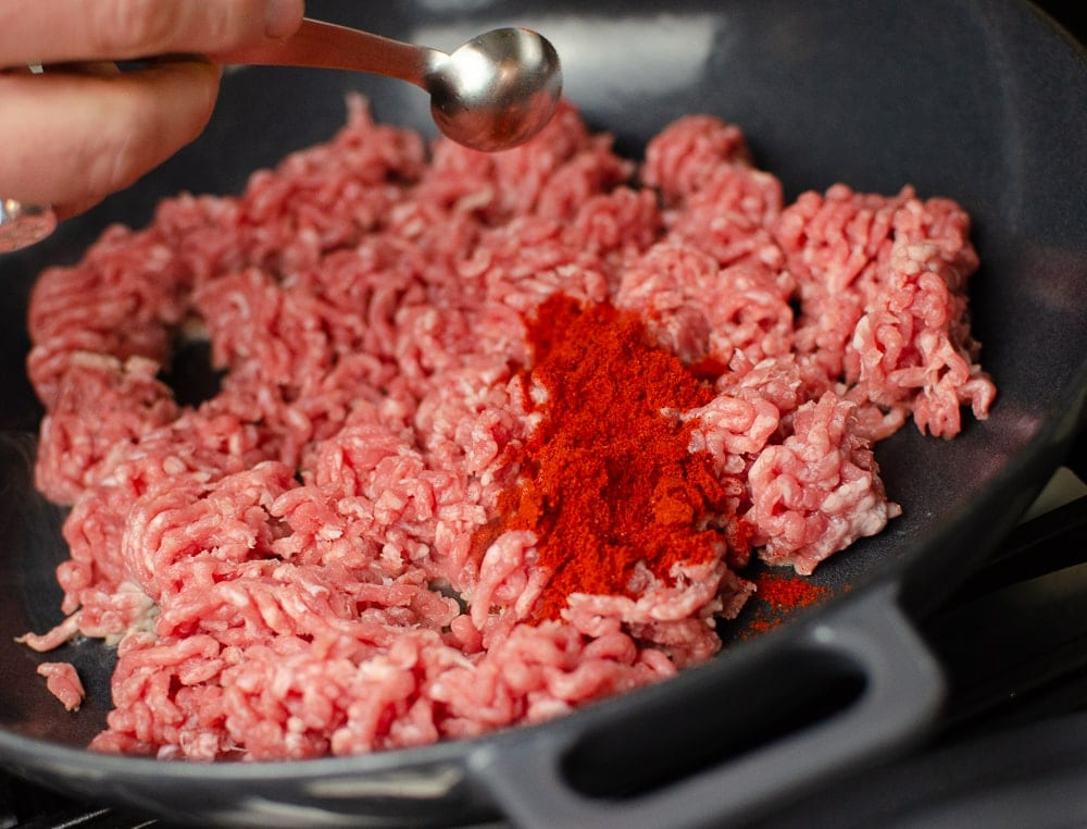 Smoked Paprika being poured over minced pork