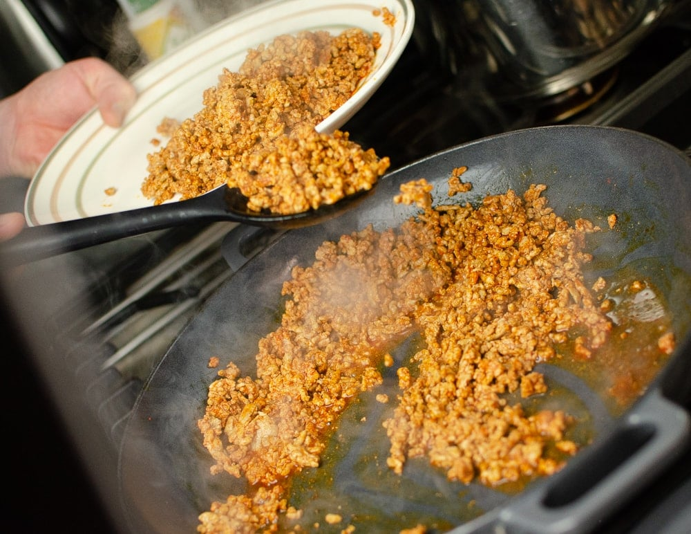 minced pork being taken out of a cast iron dish and beinfg placed onto a white plate