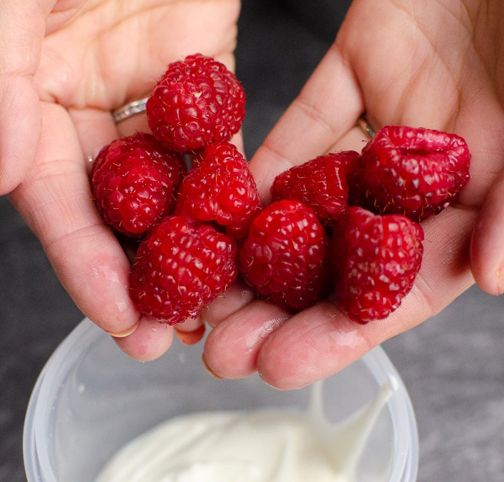 Raspberries being held after being washed to be placed into the plastic container.