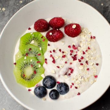 Raspberry overnight oats with fresh kiwi,raspberries,blueberries and scattered oats in a white bowl