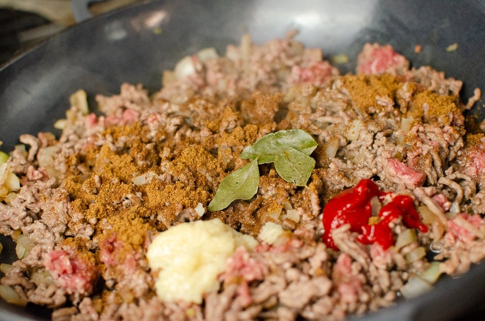 Garlic, curry leaves and chilli being added to the mince