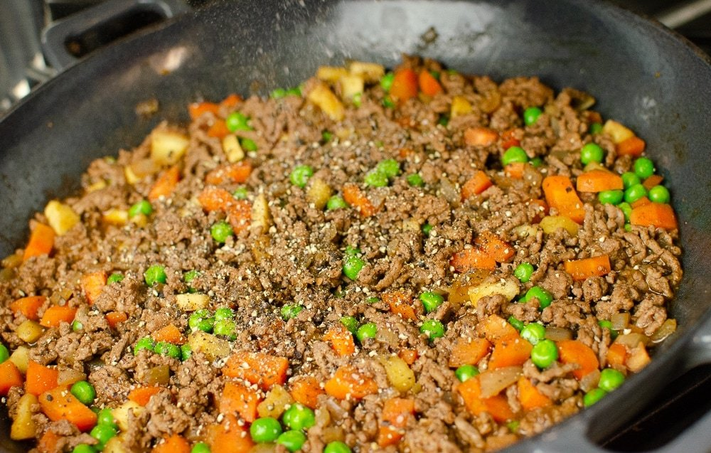 Black pepper being put on the mince.