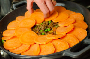 Sweet potato slice being placed on top of the mince.