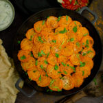 Curried Mince Hotpot in a cast iron dish ready to serve with poppadoms and Raita