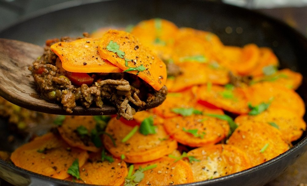 Curried Mince Hotpot with sweet potato being served up with a wooden spoon