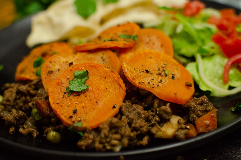 Curried mince hotpot served on a black plate with salad and poppadom.