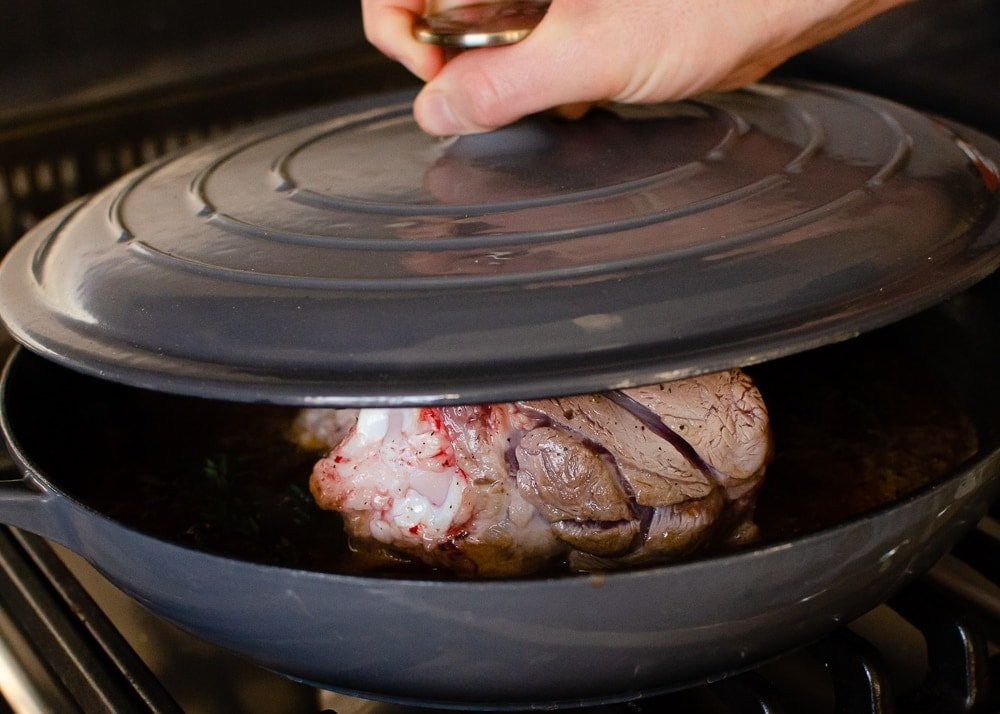 The lid being placed back on the cast iron dish to cook our lamb shanks