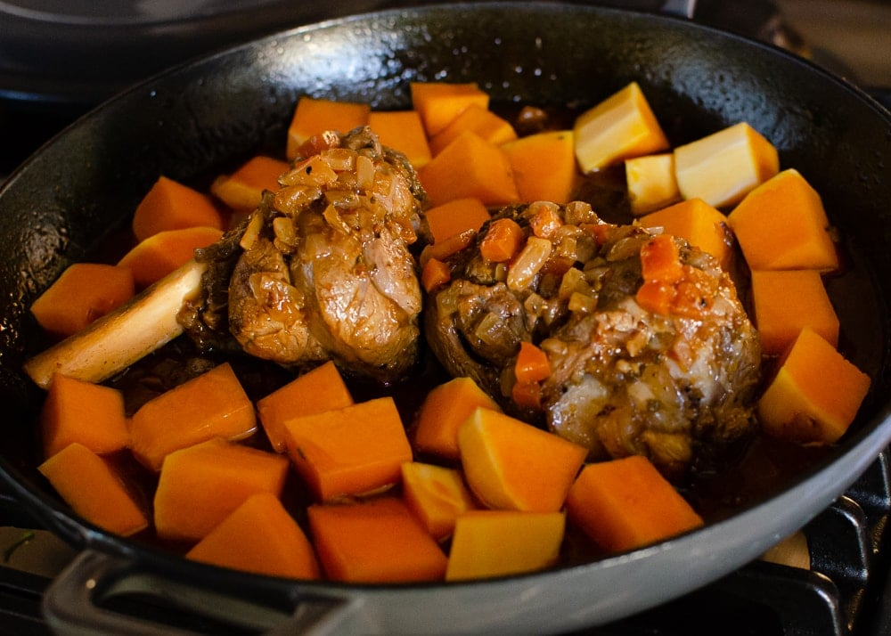 Butternut squash being added to the lamb shanks in a cast iron dish