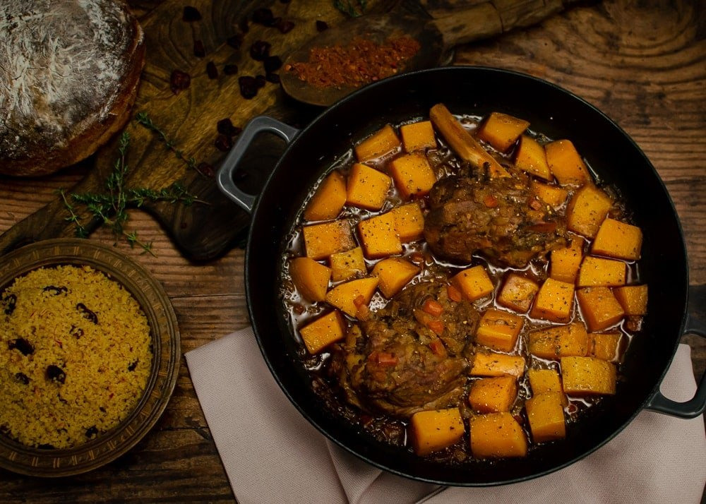 Cooked Persian Lamb Shanks with butternut Squash in a cast iron dish