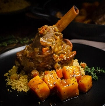 Persian Lamb Shank on black plate with a bed of cous cous with butternut squash on the side