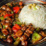 Vegan Kung Pao with red and green peppers served with white rice in a black bowl ready to be eaten