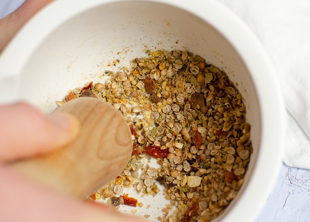 Pickling spices being crushed with a pestle and mortar