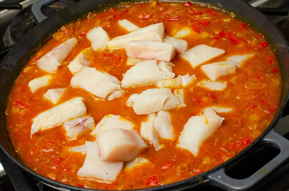 Adding the pieces of haddock to spicy fish soup