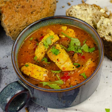 Spicy Fish Soup served in a blue bowl with crusty bread on the side