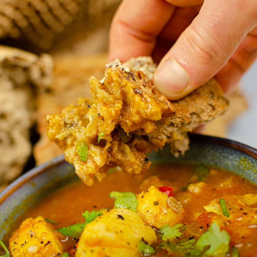 Dipping crusty bread in our spicy fish soup