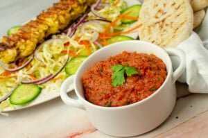 Kebab Shop Chilli Sauce in a white bowl with our chicken kebab on salad in the back ground