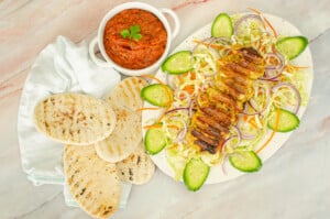 Our Takeaway chicken kebab recipe served with our salad and kebab shop chilli sauce and pitta breads on the side