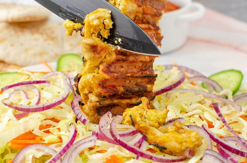Cutting strips of chicken from our takeaway chicken kebab recipe on a bed of salad