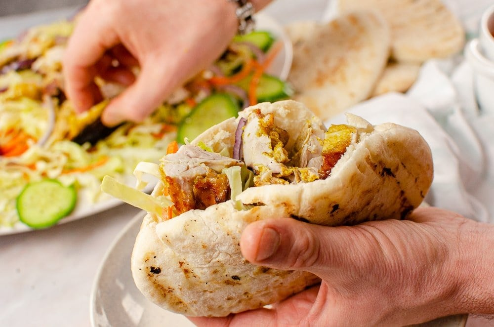 Placing our takeaway chicken kebab into a pitta bread with salad