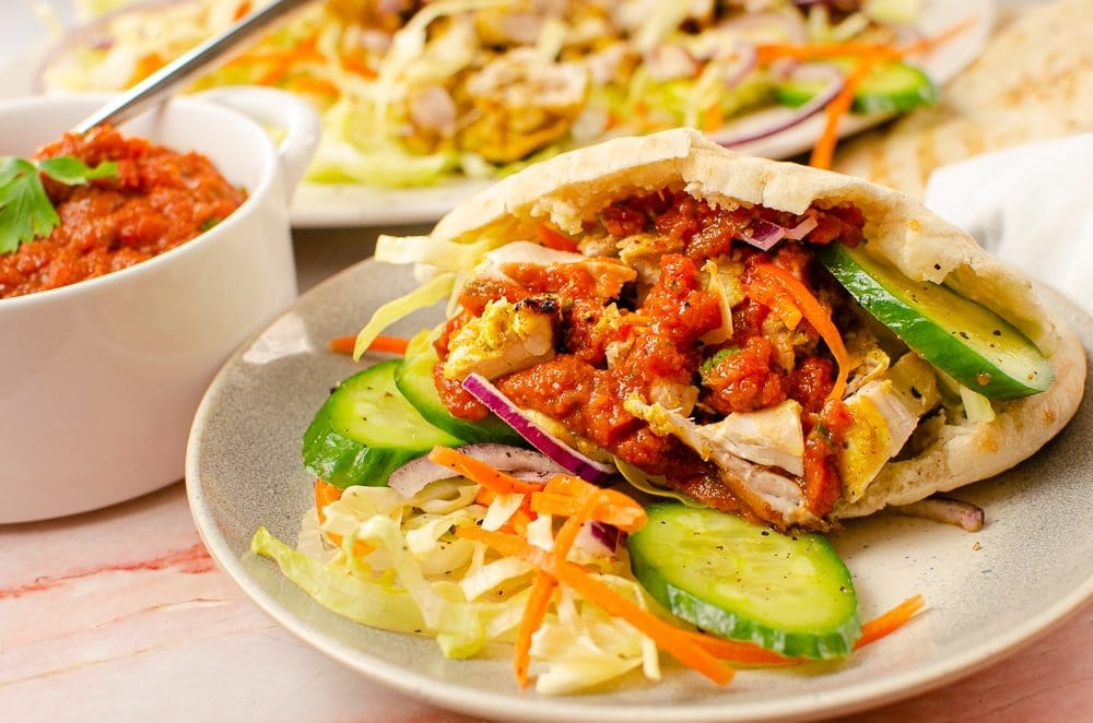 Takeaway chicken kebab recipe in a pitta bread with salad and chilli sauce on grey plate