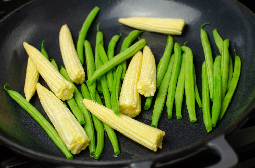 Baby corns and green beans in a cast iron dish ready to be stir-fried
