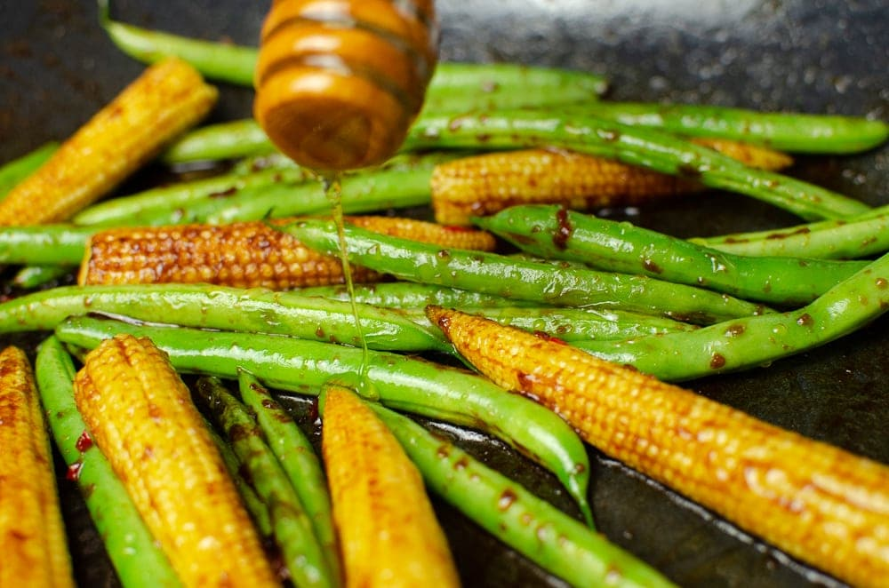 Drizzling honey over our stir-fried vegetables side dish in a cast iron pan