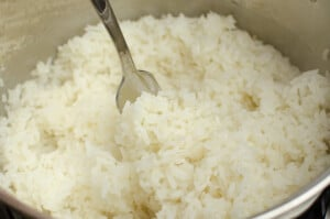 Fluffing the rice up with a silver fork before serving